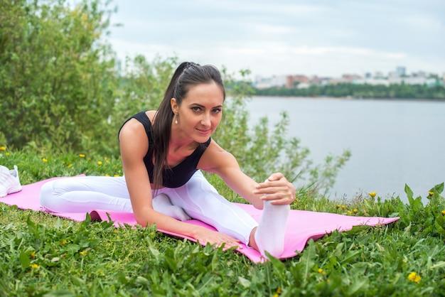 Młoda kobieta streching nogi trening uliczny, fitness, sport