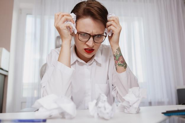 Młoda kobieta stresuje się w pracy
