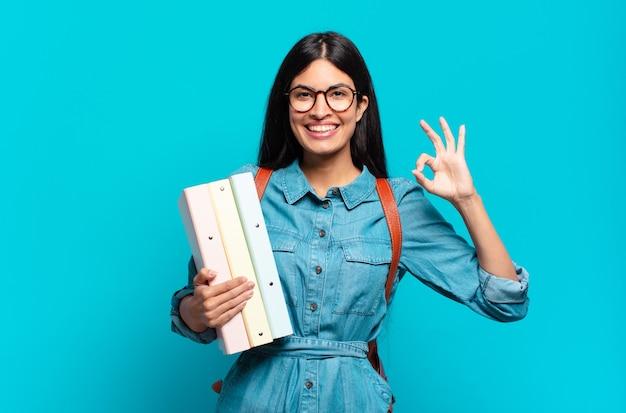 Młoda kobieta student hispanic czuje się szczęśliwa, zrelaksowana i usatysfakcjonowana, pokazując aprobatę gestem ok, uśmiechając się