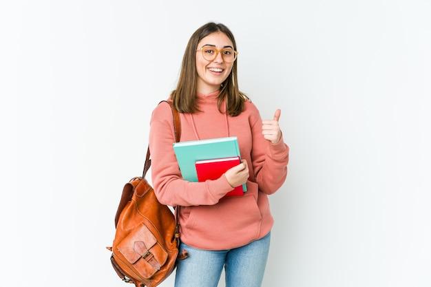 Młoda kobieta student na białym bakcground podnosząc oba kciuki do góry, uśmiechnięty i pewny siebie.