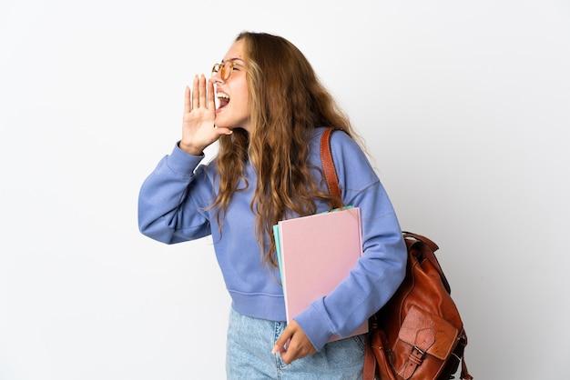Młoda kobieta student na białym tle krzycząc z szeroko otwartymi ustami na bok