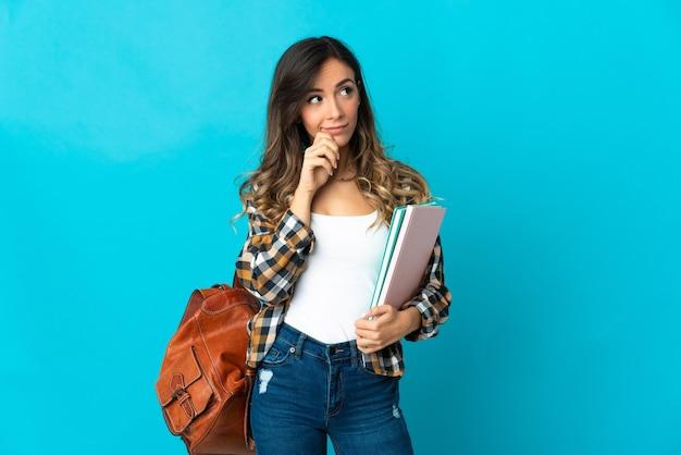 Młoda kobieta student na białym tle na niebieskiej ścianie, mając wątpliwości i myślenie