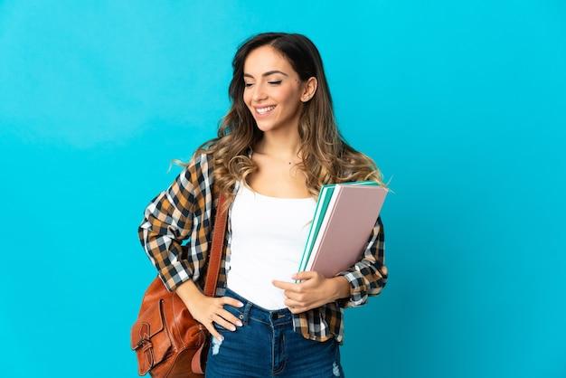 Młoda kobieta student na białym tle na niebieskiej ścianie pozowanie z rękami na biodrze i uśmiechnięty