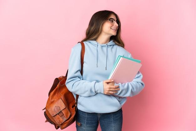 Młoda kobieta student na białym tle na różowej ścianie, patrząc z boku i uśmiechnięty