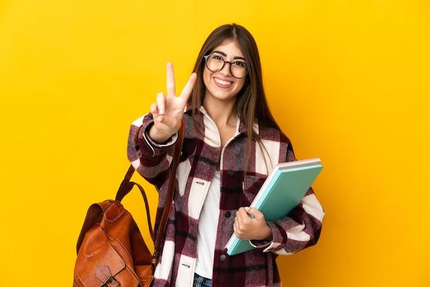 Młoda kobieta student na białym tle na żółtej ścianie, uśmiechając się i pokazując znak zwycięstwa