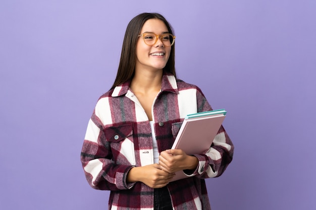 Młoda kobieta student na fioletowym tle myśli pomysł, patrząc w górę