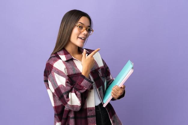 Młoda kobieta student na fioletowym tle wskazującym palcem z boku