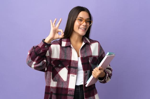 Młoda kobieta student na fioletowym tle wyświetlono znak ok palcami