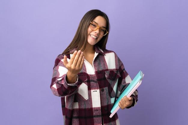 Młoda kobieta student na fioletowym tle zapraszając do przyjścia z ręką cieszę się, że przyszedłeś