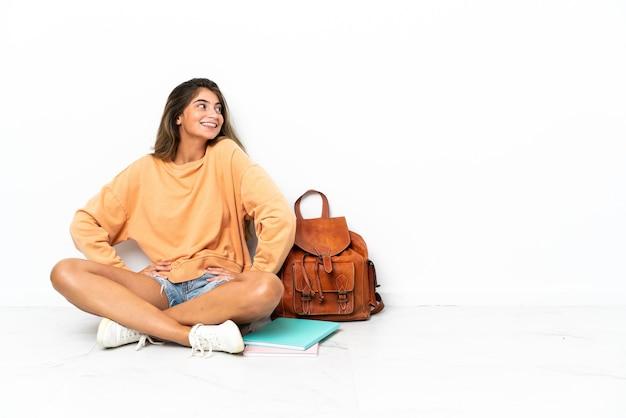 Młoda kobieta student siedzi na podłodze z laptopem na białym tle na białej ścianie, pozowanie z rękami na biodrze i uśmiecha się