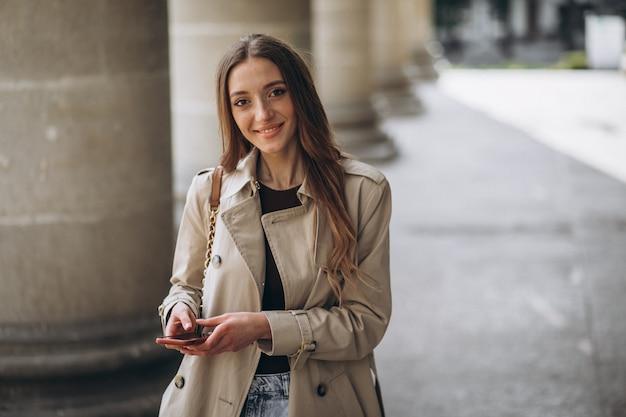 Młoda kobieta student uniwersytetu rozmawia przez telefon