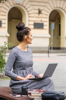 Młoda kobieta student używa laptopa na ławce na ulicy w pobliżu uniwersytetu