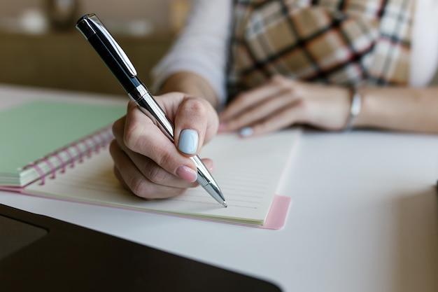 Młoda kobieta, studentka kursu elearningu na odległość, pracuje w domowym biurze i pisze treści