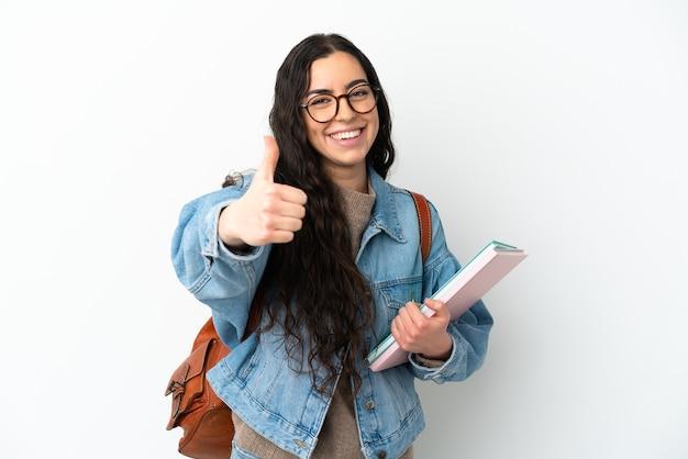 Młoda kobieta studentka na białym tle na białej ścianie z kciukami do góry, ponieważ stało się coś dobrego