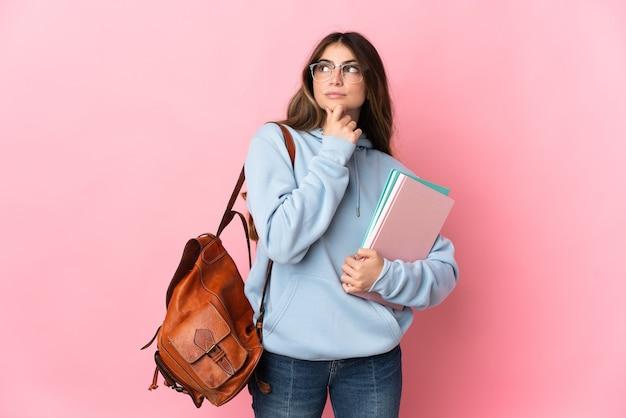 Młoda kobieta studentka na białym tle na różowej ścianie i patrząc w górę