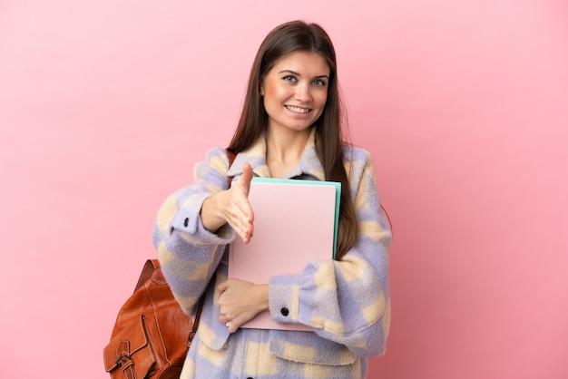 Młoda kobieta studentka na białym tle na różowym tle, ściskając ręce za zamknięcie dobrą ofertę