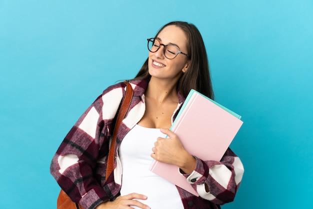 Młoda kobieta studentka na białym tle pozowanie z rękami na biodrze i uśmiechnięty