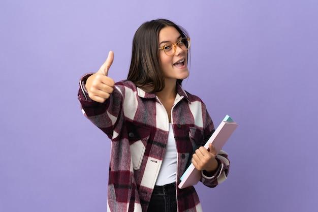 Młoda kobieta studentka na fioletowym tle z kciukami do góry, ponieważ stało się coś dobrego