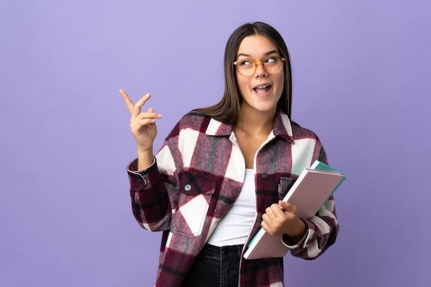 Młoda kobieta studentka odizolowana na fioletowo zamierzająca realizować rozwiązanie, podnosząc palec w górę