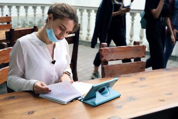 Młoda kobieta studentka siedzi na zewnątrz przy stole i pracuje z notatkami w notatniku