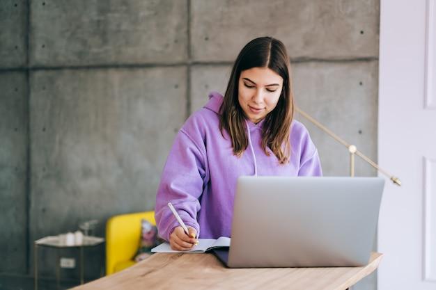 Młoda kobieta studentka studiuje z laptopem, odlegle przygotowuje się do egzaminu testowego, pisze esej, odrabianie lekcji w domu, odległa koncepcja edukacji.