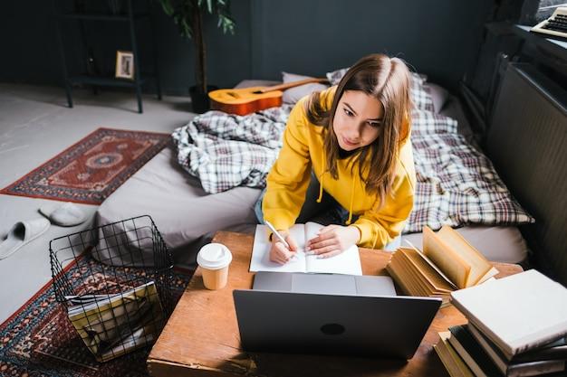 Młoda kobieta studentka studiuje z laptopem, odlegle przygotowuje się do egzaminu testowego, pisze esej, odrabianie lekcji w domu