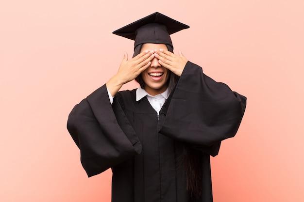 Młoda kobieta studentka uśmiecha się i czuje szczęśliwa, zakrywa oczy obiema rękami i czeka na niewiarygodną niespodziankę
