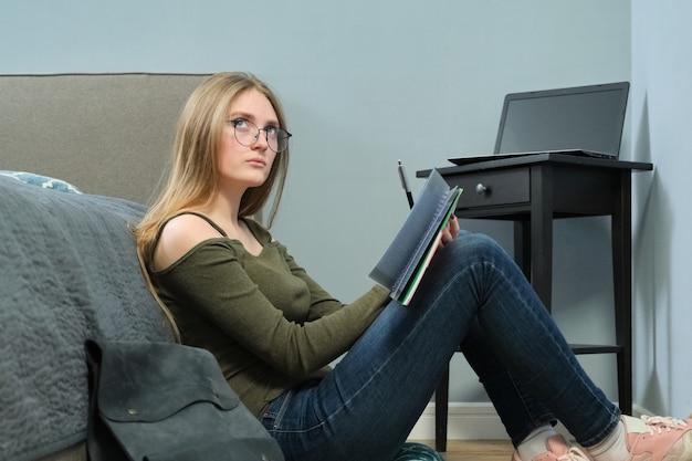 Młoda kobieta studentka z podręcznikami, czytanie i studiowanie w domu