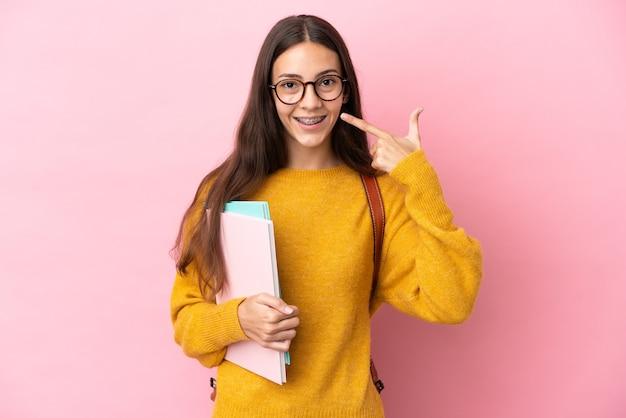 Młoda kobieta studentów na białym tle, dając kciuki do góry gest