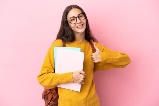 Młoda kobieta studentów na białym tle, dając kciuki do góry gestu