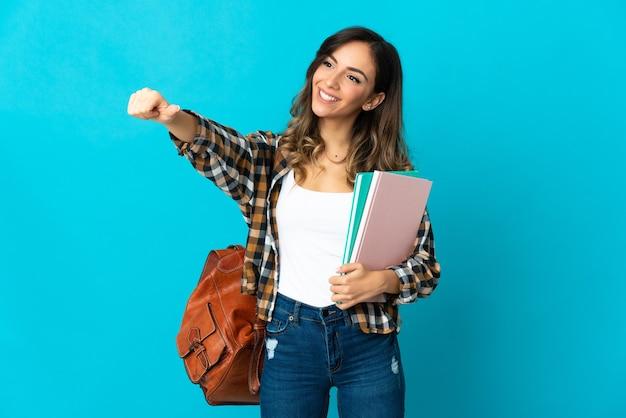 Młoda kobieta studentów na białym tle na niebieskiej ścianie, dając kciuki do góry gest