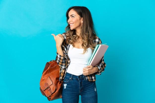 Młoda kobieta studentów na białym tle na niebieskiej ścianie, wskazując na bok, aby przedstawić produkt