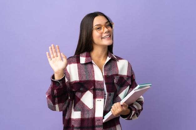 Młoda kobieta studentów na fioletowym tle salutowania ręką z happy wypowiedzi