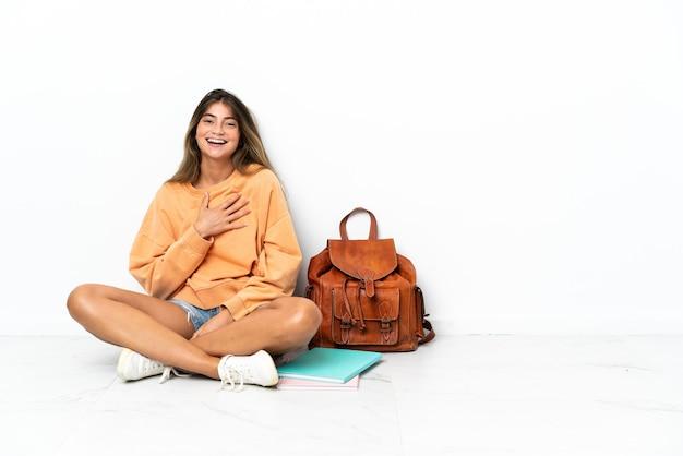 Młoda kobieta studentów siedzi na podłodze z laptopem na białym tle dużo uśmiecha się