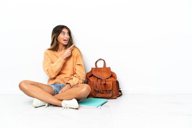 Młoda kobieta studentów siedzi na podłodze z laptopem na białym tle
