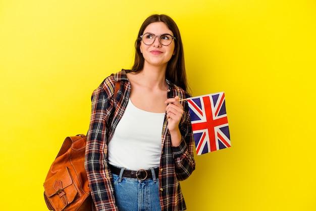 Młoda kobieta studiująca angielski na różowym tle marząca o osiągnięciu celów i celów