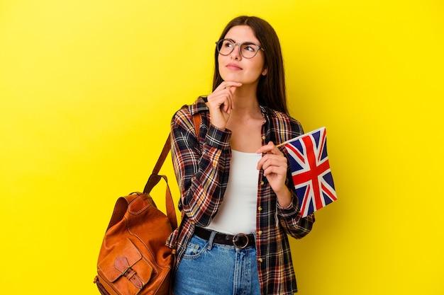 Młoda kobieta studiuje angielski na białym tle na różowej ścianie, patrząc z ukosa z wyrazem wątpliwości i sceptycyzmu.