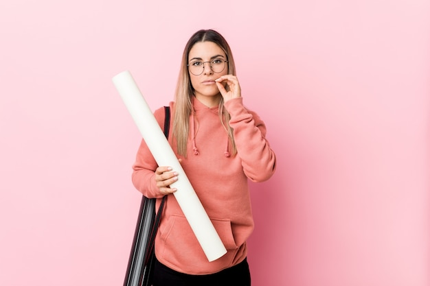 Młoda kobieta studiuje architekt z palcami na ustach, zachowując tajemnicę