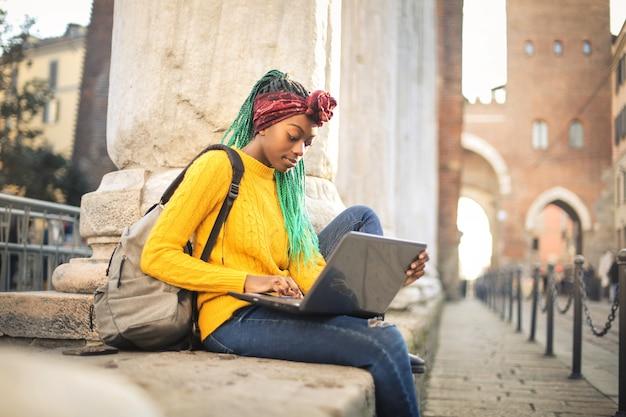 Młoda kobieta studiuje coś na swoim laptopie, siedząc na ulicy