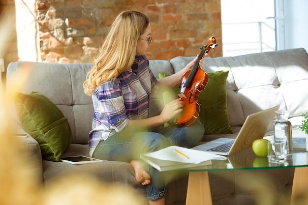 Młoda kobieta studiuje kursy muzyki online w domu.