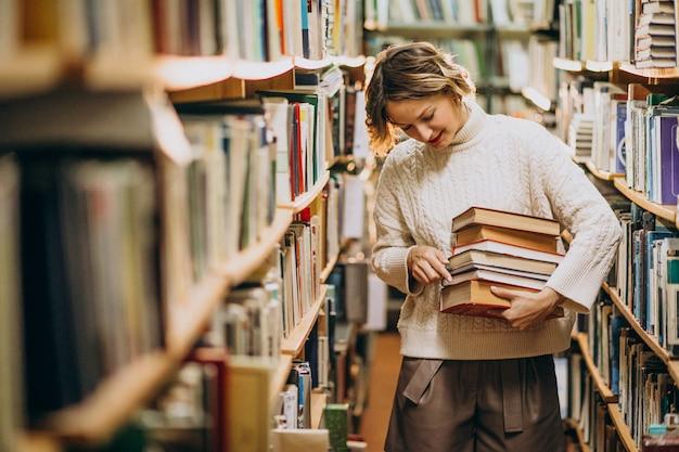 Młoda kobieta studiuje w bibliotece