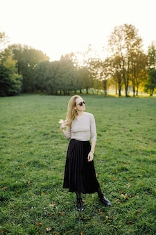 Młoda kobieta stwarzających na żółtych liści w parku jesienią. na wolnym powietrzu