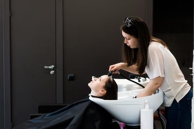 Młoda kobieta stylista suszenia włosów kobiety z wodą w salonie fryzjerskim