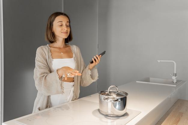 Młoda kobieta stylowa gotowanie na płycie indukcyjnej w nowoczesnej kuchni. koncepcja inteligentnych technologii urządzeń kuchennych