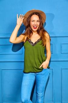 Młoda kobieta stylowa model w codzienne letnie ubrania zielone i brązowy kapelusz z czerwonymi ustami, pozowanie w pobliżu niebieską ścianą, mrugając