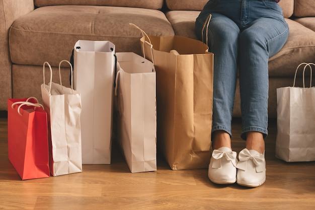 Młoda kobieta stylowe trzymając torby na zakupy i siedząc na kanapie