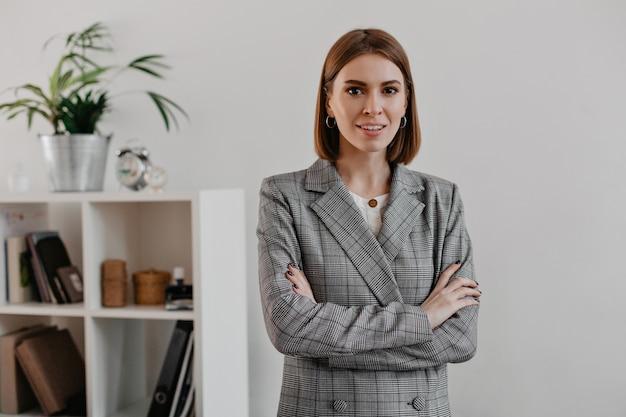 Młoda kobieta sukcesu o brązowych oczach w klasycznej szarej kurtce pozuje w jasnym biurze.