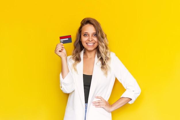 Młoda kobieta sukcesu trzymająca w ręku plastikową kartę kredytową na żółtym tle