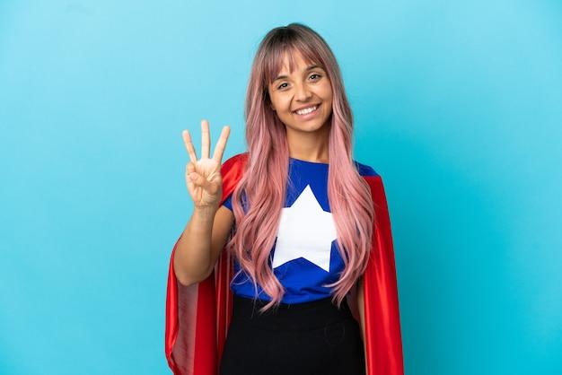 Młoda kobieta superbohatera z różowymi włosami na białym tle na niebieskim tle szczęśliwa i licząca trzy palcami