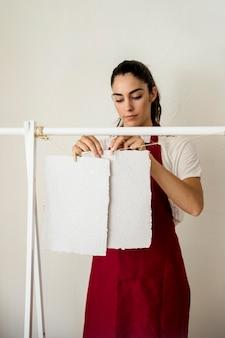 Młoda kobieta suszy handmade białego papier